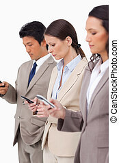 Group of businesspeople with their cellphones against a...