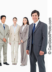 Smiling young salesman with team behind him