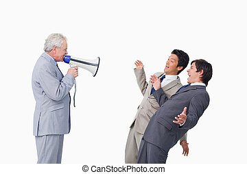 Senior businessman with megaphone yelling at his employees...