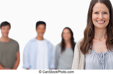 Smiling woman with her friends standing behind her