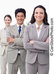 Smiling business team standing with folded arms
