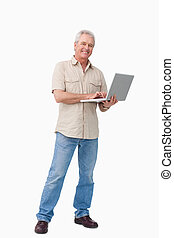 Smiling mature male with his laptop against a white...