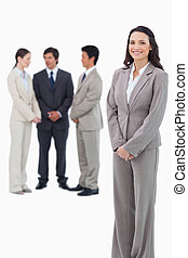 Smiling saleswoman with her team behind her
