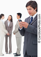 Salesman reading text message on cellphone with team behind...