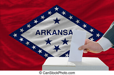 man putting ballot in a box during elections  in front of flag american state of arkansas