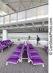 row of purple chair at airport with moving traveler