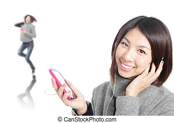 Young Happy Girl listen music with earphones by mobile phone...