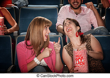 Women Laugh in a Theater - Two pretty young women in the...