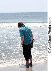Teen Boy Standing In Surf With Closed Umbrella - Back view...