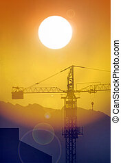 Construction crane and sun - Construction crane back lit by...