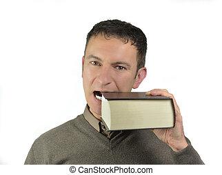 Guy biting a big book - Handsome young man bites a big book