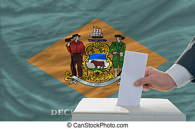 man putting ballot in a box during elections  in front of flag american state of delaware