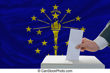 man putting ballot in a box during elections  in front of flag american state of indiana