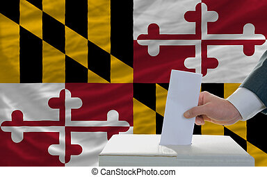 man putting ballot in a box during elections  in front of flag american state of maryland