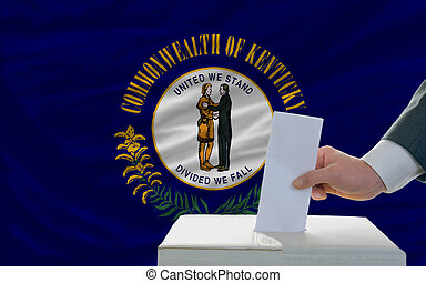 man putting ballot in a box during elections  in front of flag american state of kentucky