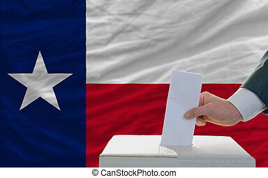 man voting on elections in front of flag US state flag of...