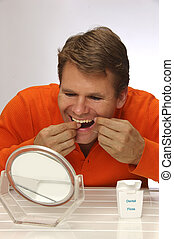 Man flossing teeth - Caucasian man flosses teeth in front of...