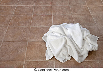 Creased white towels on ceramic floor in a laundry room or...