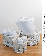 Clean towels in white wicker baskets, on a wooden surface.