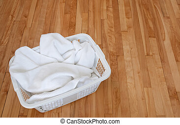 White towels in a laundry basket on wooden floor