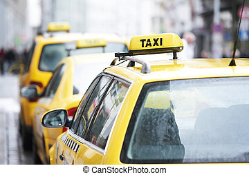 yellow taxi cab cars waiting for a client passenger in turn
