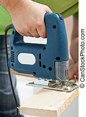 Carpenter or joiner working with electric saw