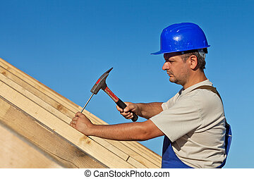 Carpenter working on the roof wooden structure - driving in...