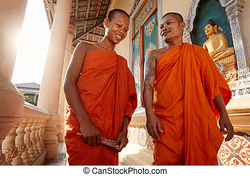 Two monks meet and salute in a buddhist monastery, Asia -...