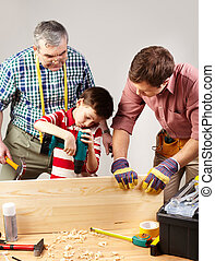 Working together - A boy working with drill under his father...
