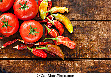 Assortment of chilli peppers and tomato on a rustic wooden...