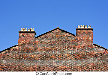 Old red brick wall with chimney pots against a clear blue sky