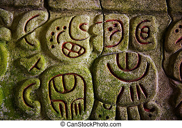 Ancient Mayan hieroglyphics in stone, from the ruins at...