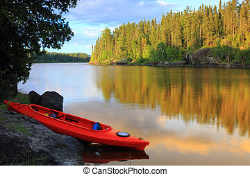 Canoe at the lake - Red canoe sitting on the rocks at the...