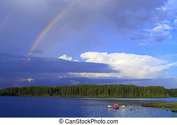 Girl canoeing - Woman canoeing in a beautiful lake with...
