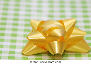 Yellow Ribbon - Close up of a Yellow ribbon over a green and...