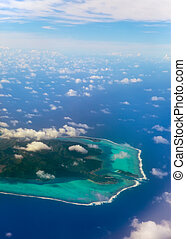 Polynesia. The atoll ring at ocean is visible through clouds. Aerial view.