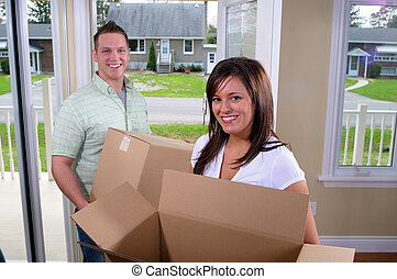 Moving House - You Couple Moving Into A New Home, Unpacking...