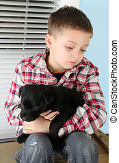 Boy and puppy - Beautiful blond boy with a black puppy