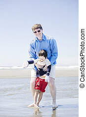 Father walking disabled son at the beach - Father walking...