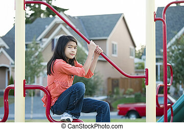 Nine year old girls playing on the bars at playground