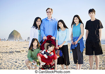 Large family of seven standing on the beach by the ocean....