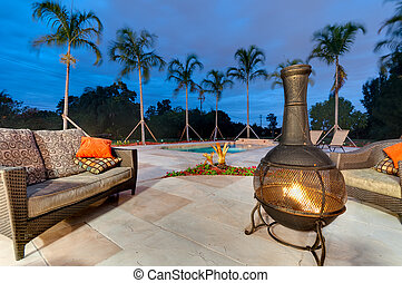Fire pit and swimming pool - Fire pit in a patio at dusk...