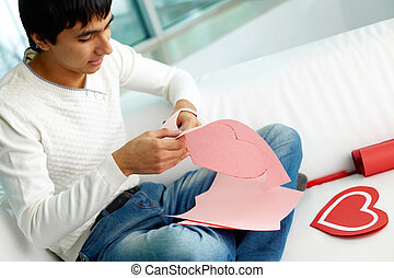 Making paper heart - Image of handsome man cutting paper...
