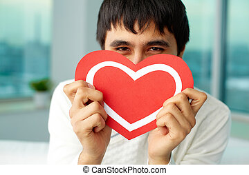 Showing heart - Portrait of happy man holding red paper...