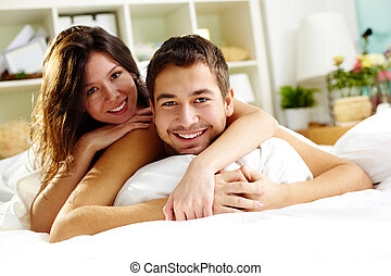 Togetherness - Happy young couple lying in bed and looking...
