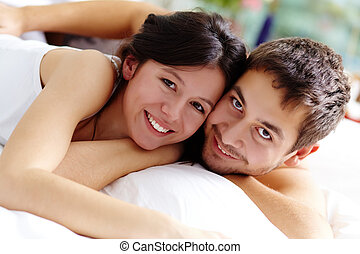 Closeness - Happy couple lying in bed and looking at camera...