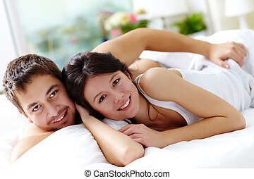 Lovers - Happy young couple lying in bed and looking at...