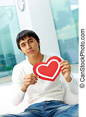 Man with paper heart - Portrait of happy man holding red...