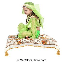 little arabian girl sitting on a flying carpet