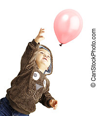 portrait of funny kid trying to hold a pink balloon over...